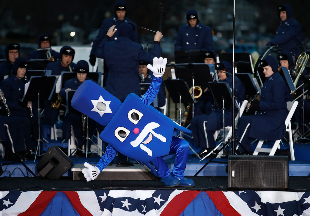 . A dreidel character falls down as it dances and spins on stage with the United States Air Force Band during the annual National Menorah Lighting, in celebration of Hanukkah, on the Ellipse near the White House in Washington, Tuesday, Dec. 12, 2017. (AP Photo/Carolyn Kaster)