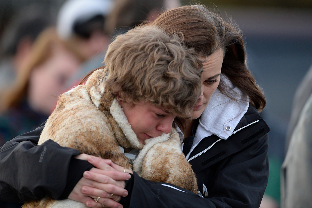 . CENTENNIAL, CO - DECEMBER 13: A mother hold on to her son outside, Shepherd of the Hills School, where frightened parents were asked to pick up their children after a gunman opened fire at Arapahoe High School, December 13, 2013. One student was critically wounded. (Photo by RJ Sangosti/The Denver Post)