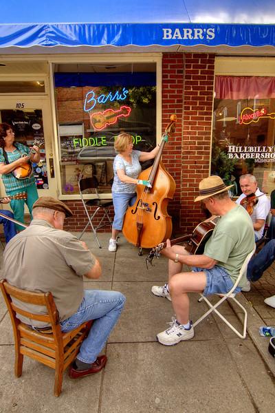 A group of people play musical instruments in front of Barr's Fiddle Shop in Galax, VA on Friday, August 9, 2013. Copyright 2013 Jason Barnette