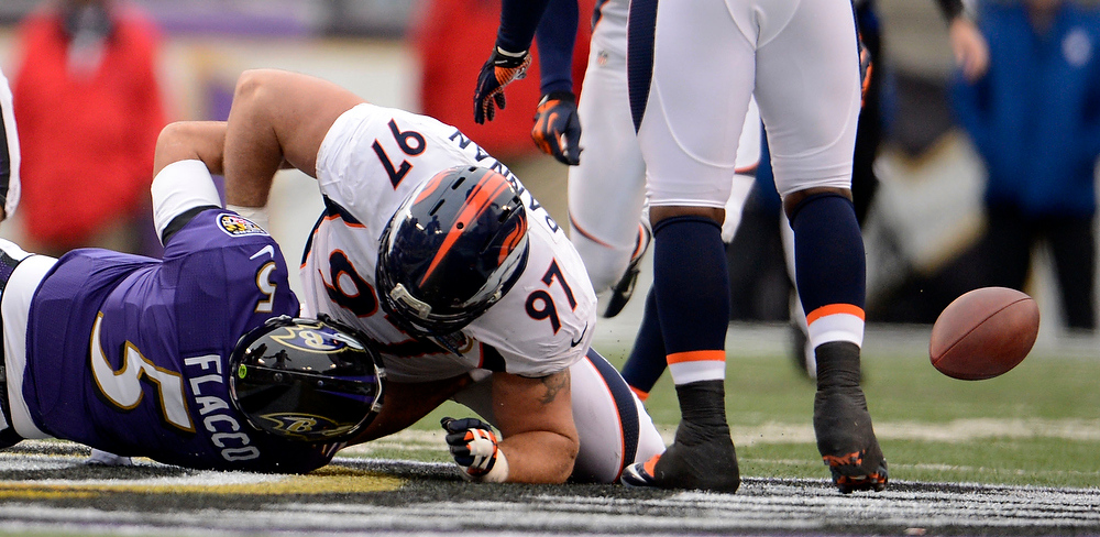 Description of . Denver Broncos defensive tackle Justin Bannan (97) forces a fumble by Baltimore Ravens quarterback Joe Flacco (5) during the first quarter Sunday, December 16, 2012 at M&T Bank Stadium. John Leyba, The Denver Post