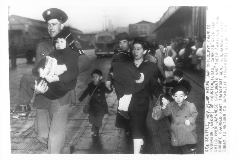 """""""MP Helps Jap Child -- Pvt. Charles Robinson of Houston, Texas, carried sick Jap child when Japanese diplomats and their families from Europe boarded Army transport gen. G.M. Randall in Seattle today to return to Japan.""""--caption on photograph"""