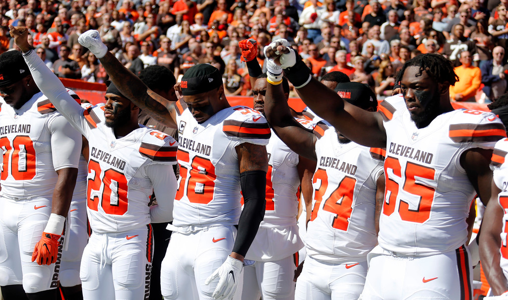 . Cleveland Browns teammates raise their fists during the national anthem before an NFL football game against the Cincinnati Bengals, Sunday, Oct. 1, 2017, in Cleveland. (AP Photo/Ron Schwane)
