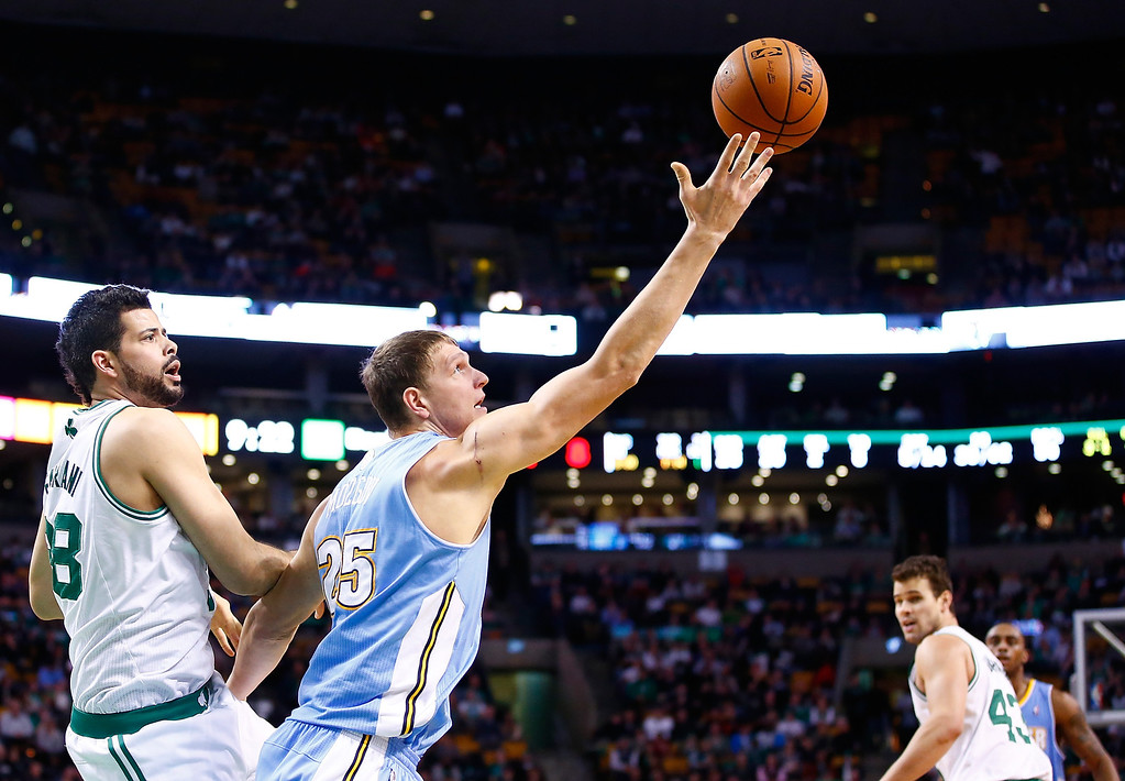 . BOSTON, MA - DECEMBER 06: Timofey Mozgov #25 of the Denver Nuggets reaches for a loose ball in the second half in front of Vitor Faverani #38 of the Boston Celtics during the game at TD Garden on December 6, 2013 in Boston, Massachusetts.  (Photo by Jared Wickerham/Getty Images)