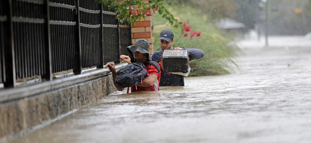 . Residents wade through floodwaters from Tropical Storm Harvey Sunday, Aug. 27, 2017, in Houston, Texas. (AP Photo/David J. Phillip)
