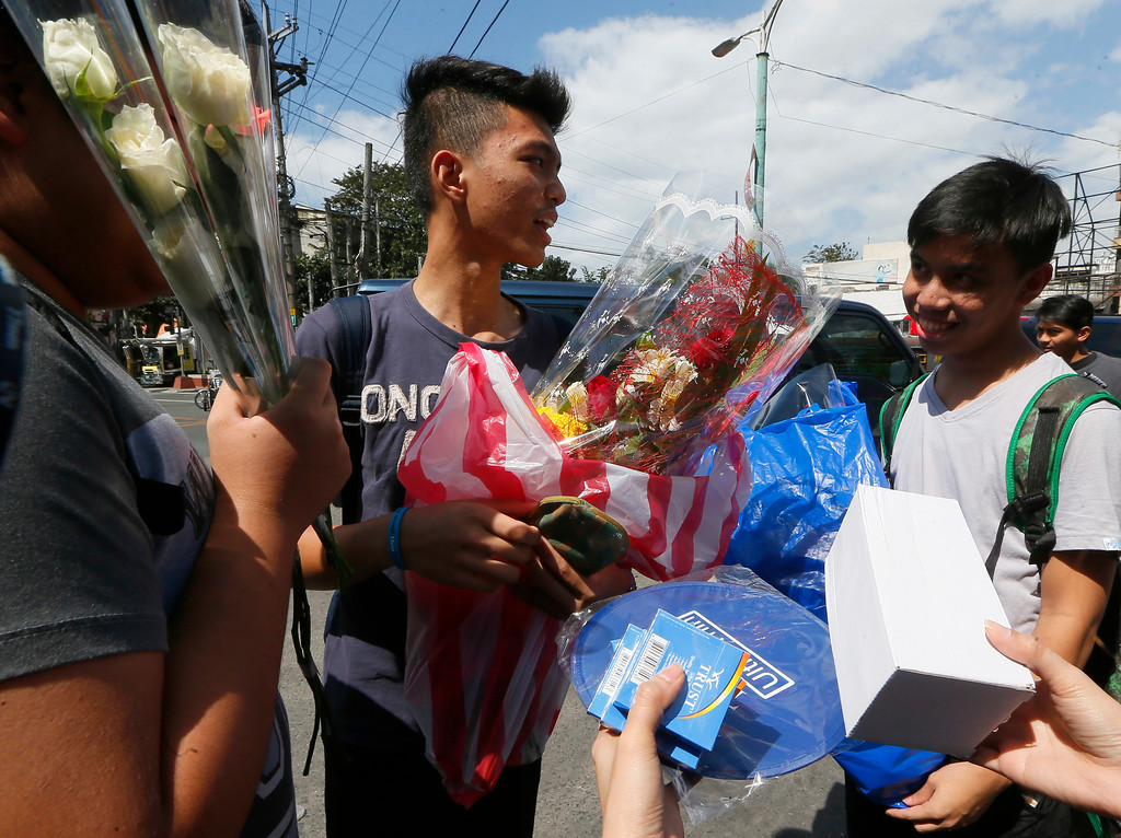 . Customers are offered condoms after buying flowers for their loved ones in celebration of Valentine\'s Day, Tuesday, Feb. 14, 2017 in Manila, Philippines. Valentine\'s Day, associated with love and romance, oftentimes are expressed with flowers, chocolates, balloons and dinner dates. (AP Photo/Bullit Marquez)