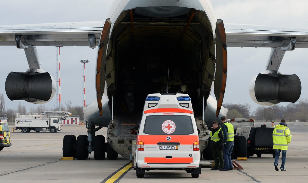 . Helpers stand next to an ambulance that is loaded into a transport aircraft on the airport Schoenefeld, near Berlin, on  March 15, 2014. The German chapter of aid organization Red Cross sends relief assistance goods to Ukraine to support the Ukrainian chapter of the Red Cross. AFP PHOTO /DPA/  RALF HIRSCHBERGER    /AFP/Getty Images