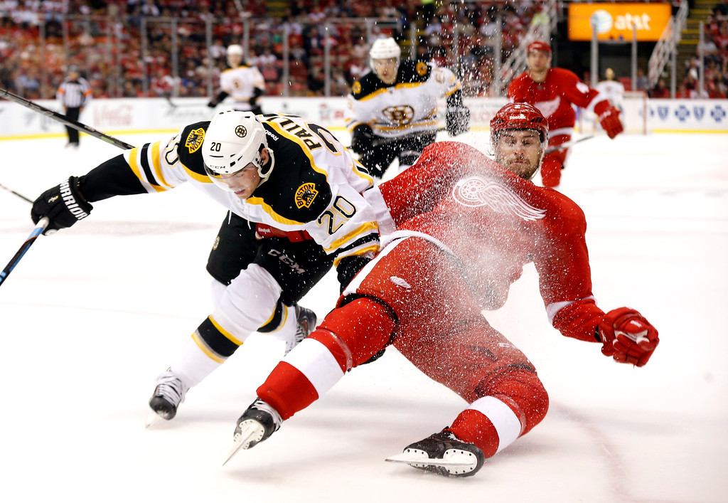 . Boston Bruins left wing Daniel Paille (20) and Detroit Red Wings defenseman Brendan Smith (2) battle for the puck in the third period of an NHL hockey game in Detroit Thursday, Oct. 9, 2014. (AP Photo/Paul Sancya)