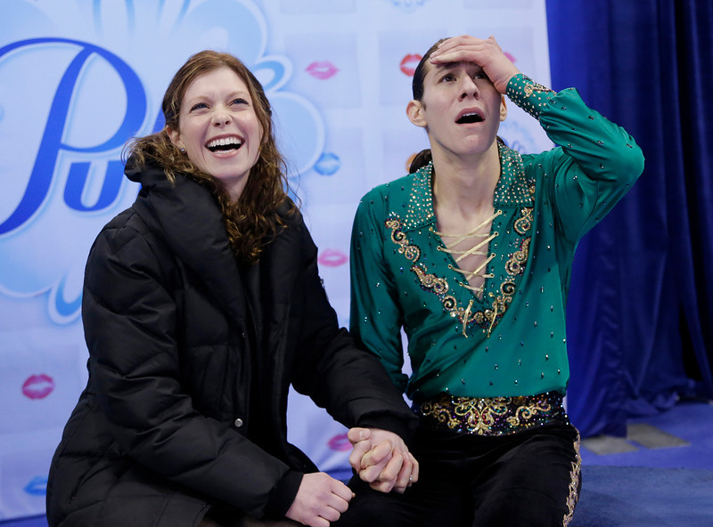 . Jason Brown, right, celebrates with his coach Kori Ade, left, as he learns his scores after competing in the men\'s free skate at the U.S. Figure Skating Championships Sunday, Jan. 12, 2014 in Boston. (AP Photo/Steven Senne)