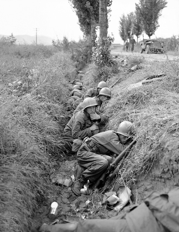 . American troops and some South Koreans are in a ditch along the road running near the Naktong River in South Korea on Sept. 19, 1950. Its known as the river road. They are in the ditch for protection against enemy shells. (AP Photo/Gene Herrick )