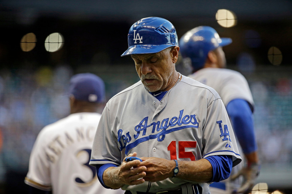 . Los Angeles Dodgers first base coach Davey Lopes looks at a stopwatch during the second inning of a baseball game against the Milwaukee Brewers Tuesday, May 21, 2013, in Milwaukee. (AP Photo/Morry Gash)