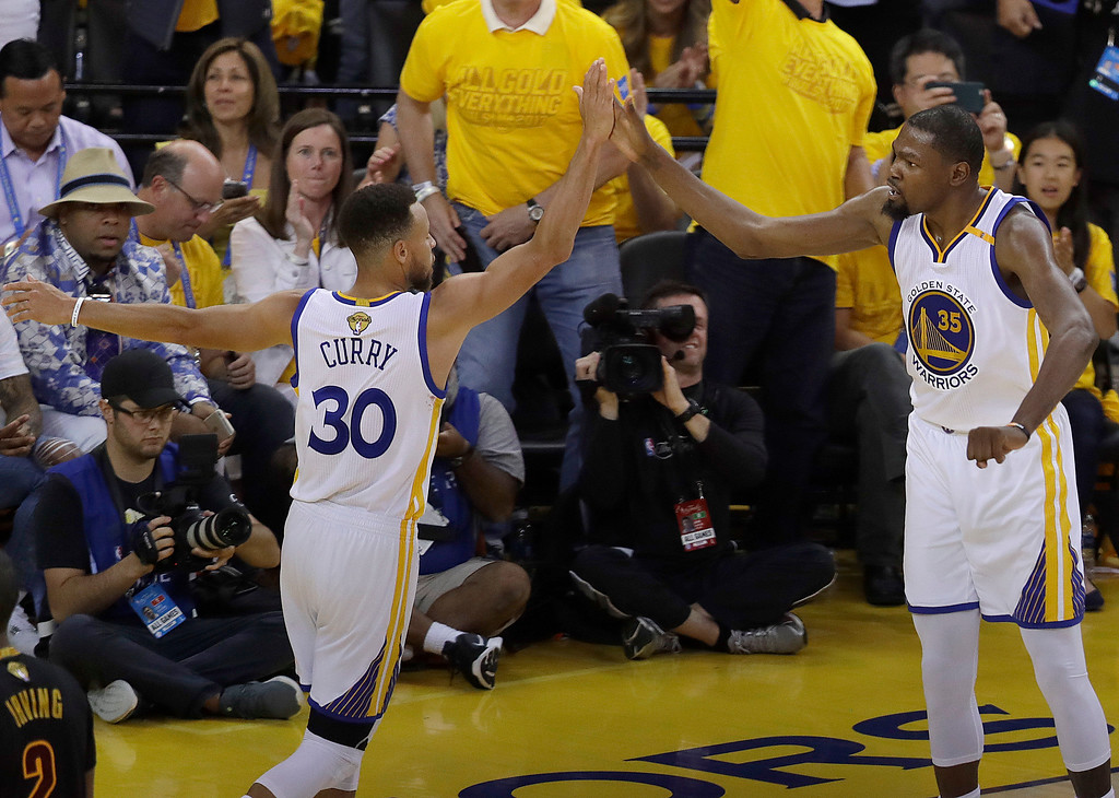 . Golden State Warriors forward Kevin Durant (35) and guard Stephen Curry (30) celebrate during the second half of Game 2 of basketball\'s NBA Finals against the Cleveland Cavaliers in Oakland, Calif., Sunday, June 4, 2017. (AP Photo/Marcio Jose Sanchez)