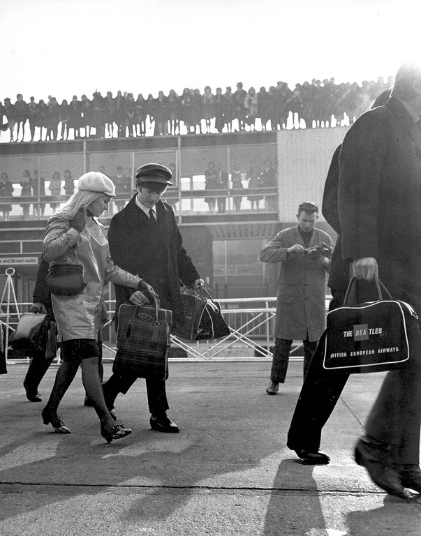 . John Lennon and his wife, Cynthia, 24, walk toward their plane with the other members of The Beatles as fans look on at London Airport in London, England, on Feb. 7, 1964.  (AP Photo/Victor Boyton)