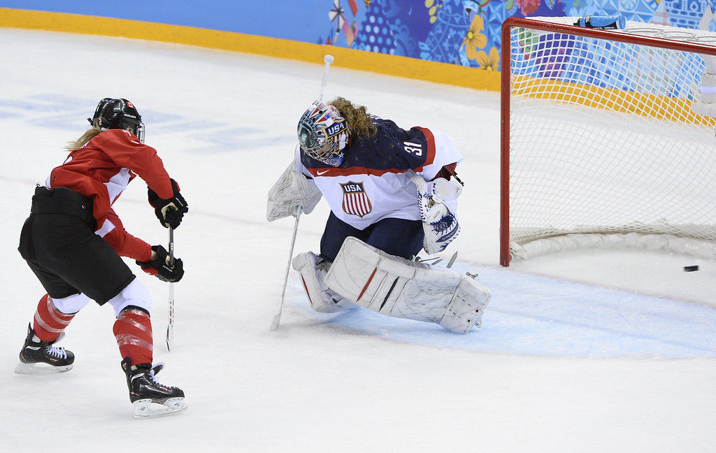 . Canada\'s Meghan Agosta-Marciano (L) scores a goal  past US goalkeeper Jessie Vetter during the Women\'s Ice Hockey Group A match between Canada and USA at the Sochi Winter Olympics on February 12, 2014 at the Shayba Arena. AFP PHOTO / JONATHAN NACKSTRAND/AFP/Getty Images