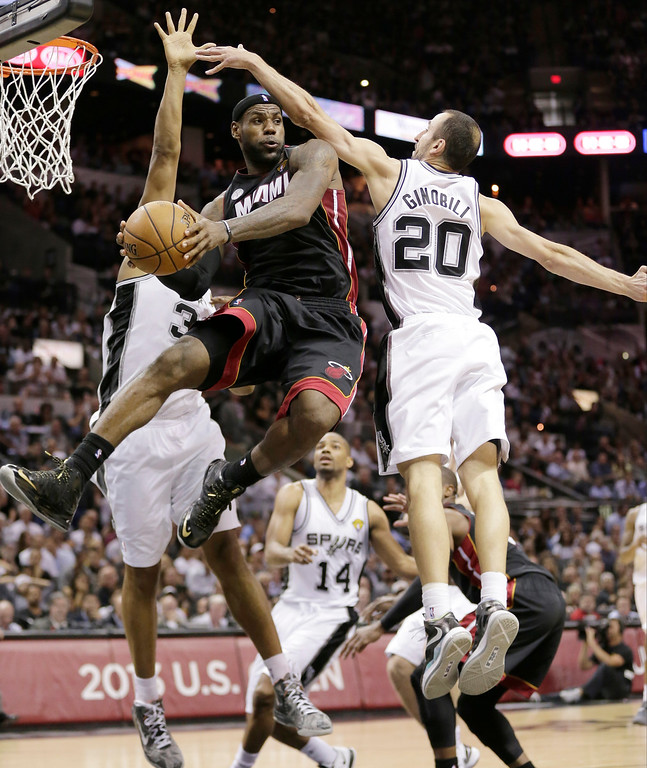 . Miami Heat\'s LeBron James (6) passes between San Antonio Spurs\' Boris Diaw (33), of France,   and Manu Ginobili (20), of Argentina, during the second half at Game 4 of the NBA Finals basketball series, Thursday, June 13, 2013, in San Antonio. (AP Photo/Eric Gay)