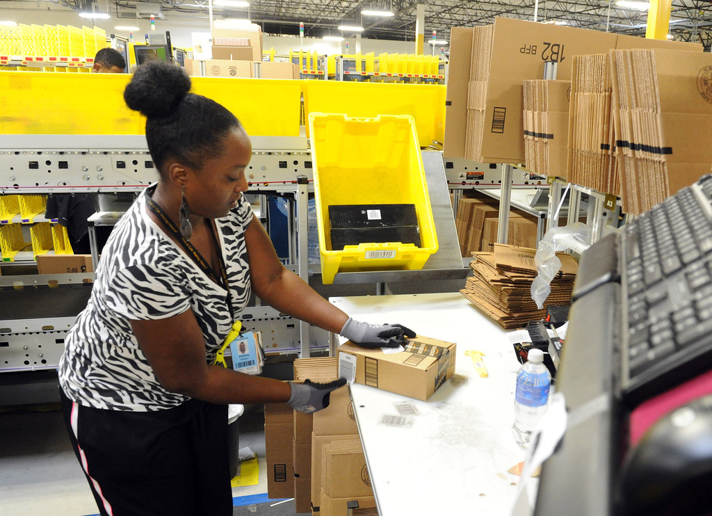 . Amazon\'s Daisha Stewart, prepares merchandise to be send out at the Amazon Fulfillment Center in San Bernardino, CA., Oct. 28, 2013.  The Amazon Fulfillment Center opened up a year ago with only half of the facility operating for business, now with the the million-square-foot center complete they will host a grand opening on Tuesday, with Gov. Jerry Brown in attendence.  This distribution center has been celebrated in San Bernardino and at the state level as an example of job creation and growth. (John Valenzuela/Staff Photographer)  (John Valenzuela/Staff Photographer)