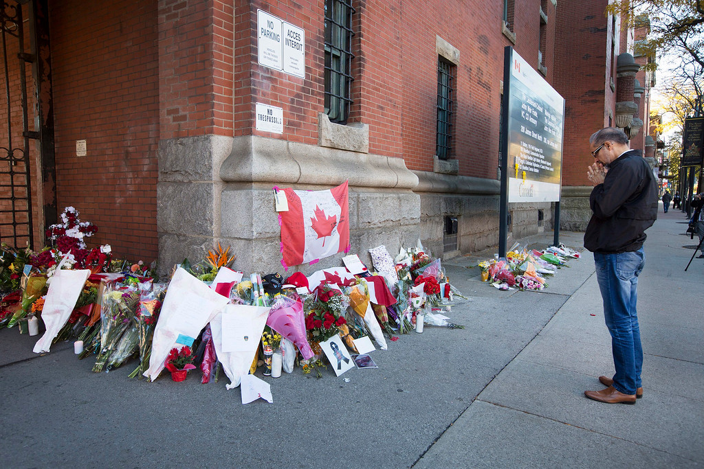 . Harry Dhaliwal  says a quick prayer after leaving some flowers and a note at a makeshift memorial to Cpl. Nathan Cirillo outside of The Lieutenant-Colonel John Weir Foote Armoury in Hamilton, Ontario on Thursday, Oct. 23, 2014.  Cirillo was shot dead at the National War Memorial by Michael Zehaf Bibeau on Wednesday.  (AP Photo/The Canadian Press, Peter Power)