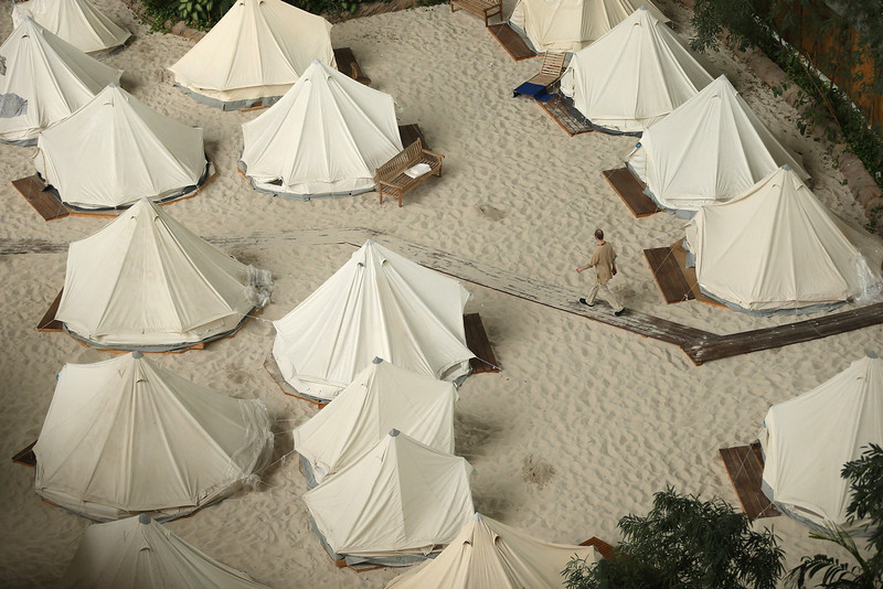 . A maintenance worker walks past tents used for overnight guests at the Tropical Islands indoor resort on February 15, 2013 in Krausnick, Germany. Located on the site of a former Soviet military air base, the resort occupies a hangar built originally to house airships designed to haul long-distance cargo. Tropical Islands opened to the public in 2004 and offers visitors a tropical getaway complete with exotic flora and fauna, a beach, lagoon, restaurants, water slide, evening shows, sauna, adventure park and overnights stays ranging from rudimentary to luxury. The hangar, which is 360 metres long, 210 metres wide and 107 metres high, is tall enough to enclose the Statue of Liberty.  (Photo by Sean Gallup/Getty Images)