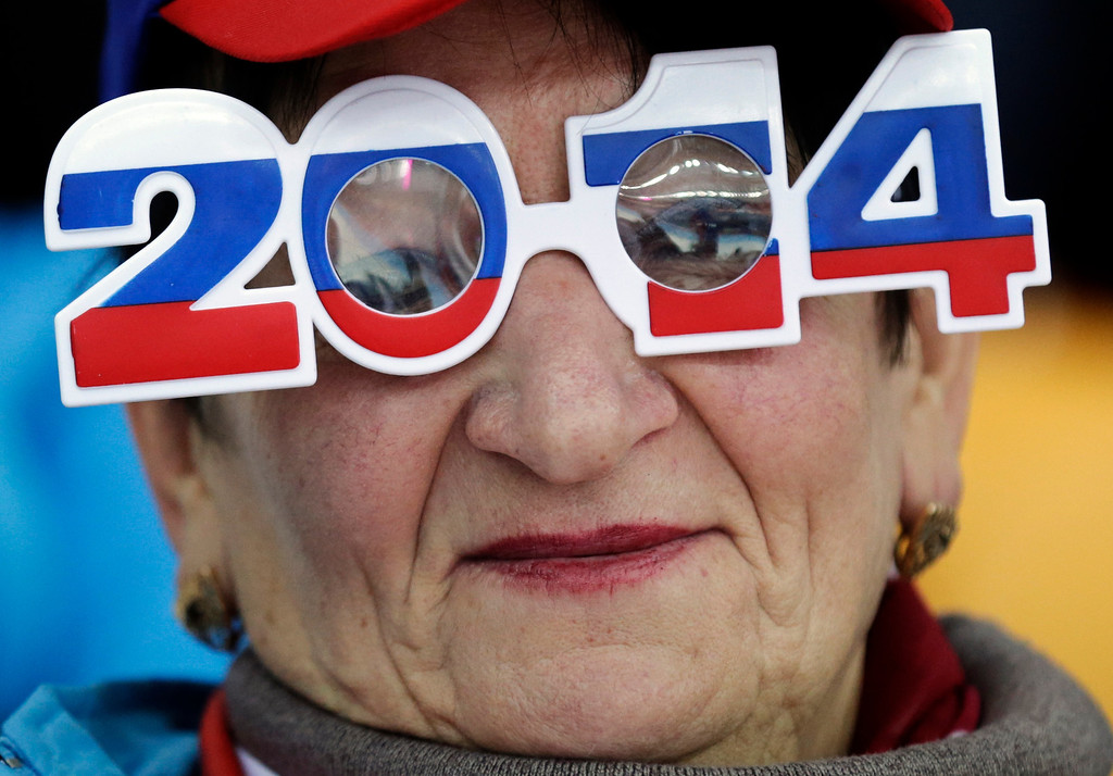 . A skating fan wears glasses in the colors of the Russian flag as she watches the men\'s 500-meter speedskating race at the Adler Arena Skating Center during the 2014 Winter Olympics, Monday, Feb. 10, 2014, in Sochi, Russia. (AP Photo/Matt Dunham)
