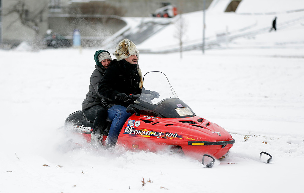 . Kelley Wing rides on the back of Sonny Dalesandro\'s snow mobile at Veteran\'s Park Friday, Dec.  6, 2013, in Tulsa, Okla. Preliminary estimates from the National Weather Service show that much of central and south-central Oklahoma, including Oklahoma City, received 2 to 4 inches of snow overnight. Northern portions of the state, including Enid and Ponca City, saw a dusting of snow.  (AP Photo/Tulsa World, Mike Simons)