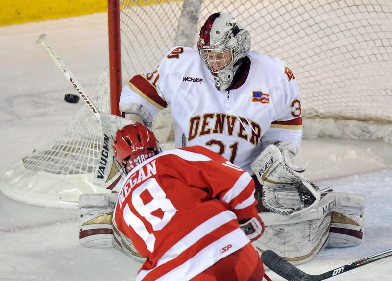 . University of Denver goalie Juho Olkinuora (31), top, saves the goal from a shot by Boston University\'s Wade Megan (18) in the 2nd period of the game at Magness Arena in Denver, Colo. on Saturday, December 29, 2012. Hyoung Chang, The Denver Post