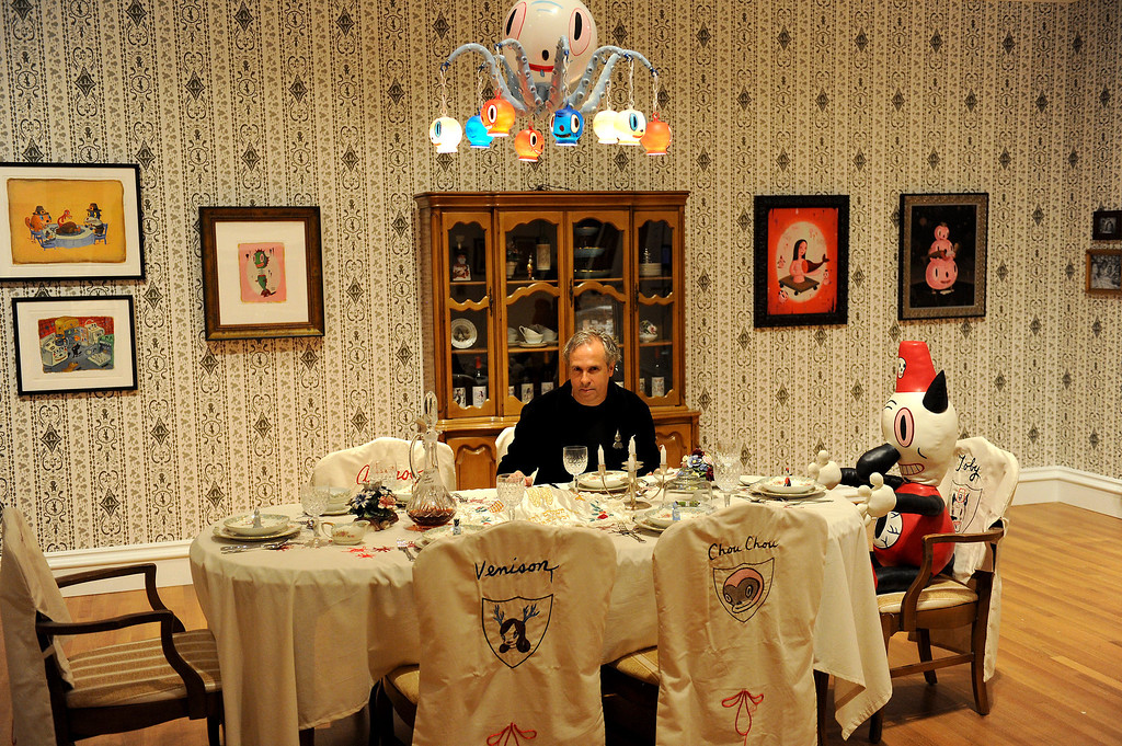 """. Gary Baseman sits at the table in the dining room of the exhibition \""""Gary Baseman: The Door is Always Open,\"""" at the Skirball Cultural Center, Wednesday, April 24, 2013. Baseman\'s work is known for his vibrant, cartoon-like, artistic style in publications such as The New Yorker, Rolling Stone and the LA Times. He designed for the game Cranium and created the animated TV series, Teacher�s Pet.The exhibition design is based on his childhood home in LA�s Fairfax district and includes family furniture and snapshots and many items of interior décor designed by the artist, including wallpaper, pillows, a chandelier and more. (Michael Owen Baker/Staff Photographer)"""