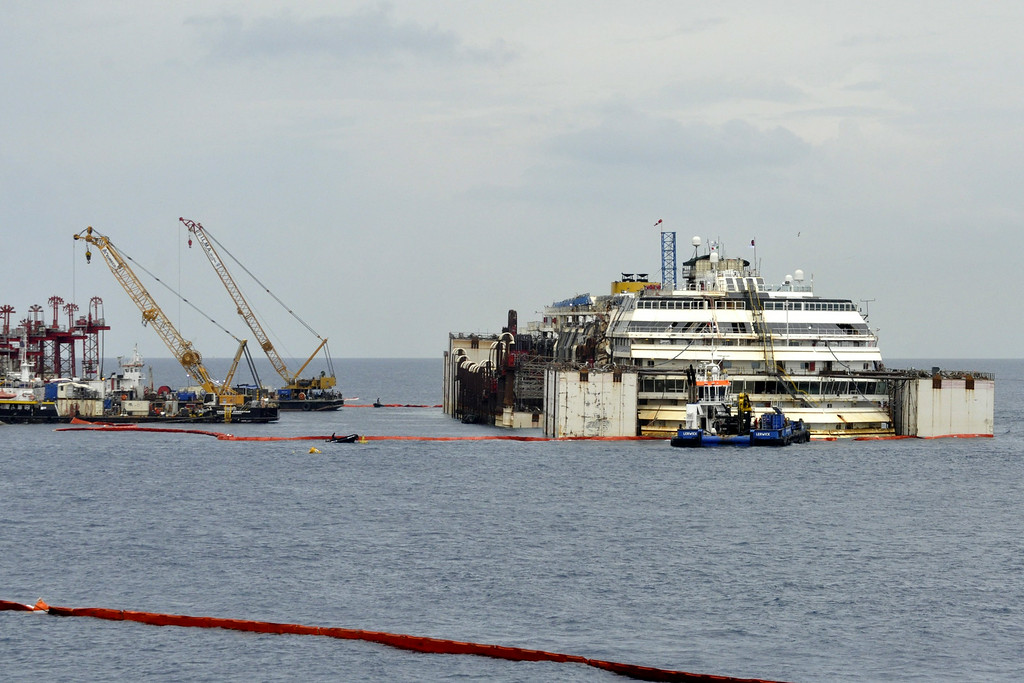 . The luxury cruise ship Costa Concordia  is seen as it moves away from the underwater platform where it laid during operations to put it afloat, on the tiny Tuscan island of Giglio, Italy, Monday, July 14, 2014.  The shipwrecked Costa Concordia has been successfully put afloat in preparation to tow it away for scrapping. Authorities expressed satisfaction that the operation to float the Concordia from an underwater platform had proceeded without a hitch early Monday. The cruise liner struck a reef in January 2012 and capsized, killing 32 people. (AP Photo/Giacomo Aprili)