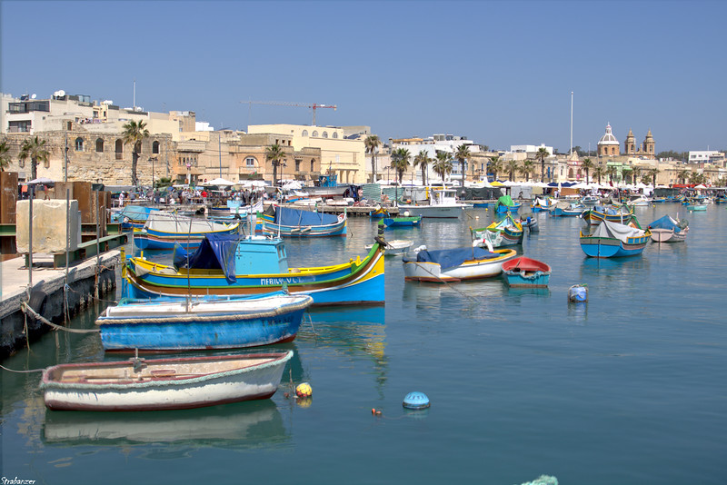 Malta.   Marsaxlokk Waterfront    03/24/19.    The brightly painted   Luzzus with their double-ended hulls. This work is licensed under a Creative Commons Attribution- NonCommercial 4.0 International License