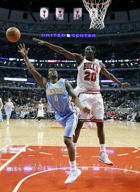 . Denver Nuggets guard Aaron Brooks (0) shoots past the out stretched arm of Chicago Bulls guard Tony Snell during the second half of an NBA basketball game, Friday, Feb. 21, 2014, in Chicago. The Bulls won 117-89. (AP Photo/Charles Rex Arbogast)