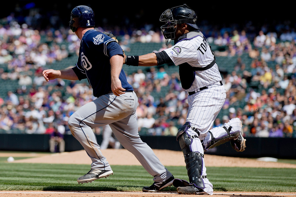 . Catcher Yorvit Torrealba #8 of the Colorado Rockies tags out Jedd Gyorko #9 of the San Diego Padres in a run-down near third base during the sixth inning at Coors Field on August 14, 2013 in Denver, Colorado.  The Rockies defeated the Padres 4-2.  (Photo by Justin Edmonds/Getty Images)