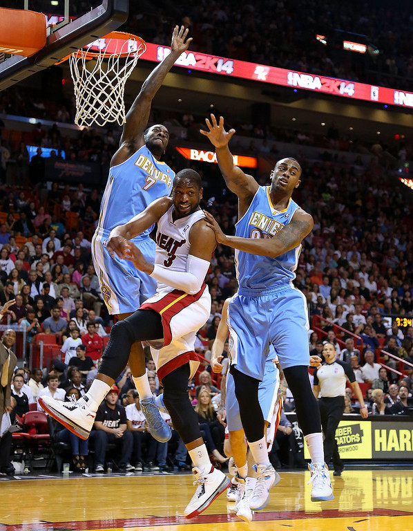 . MIAMI, FL - MARCH 14: Dwyane Wade #3 of the Miami Heat passes out of trouble against J.J. Hickson #7 and Darrell Arthur #00 of the Denver Nuggets during a game  at American Airlines Arena on March 14, 2014 in Miami, Florida. (Photo by Mike Ehrmann/Getty Images)