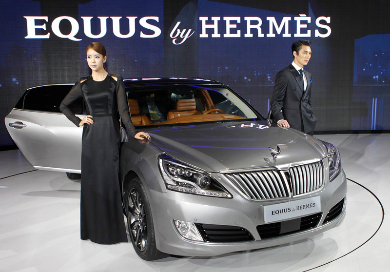 . Models pose next to Hyundai Motor\'s Equus Hermes at the Seoul motor show, in Goyang, north of Seoul March 28, 2013. South Korean carmaker Hyundai Motor hopes a touch of Hermes will make its priciest sedan as desirable as the French retailer\'s exclusive handbags and catapult its cachet into the same league as luxury European rivals. REUTERS/Lee Jae-Won