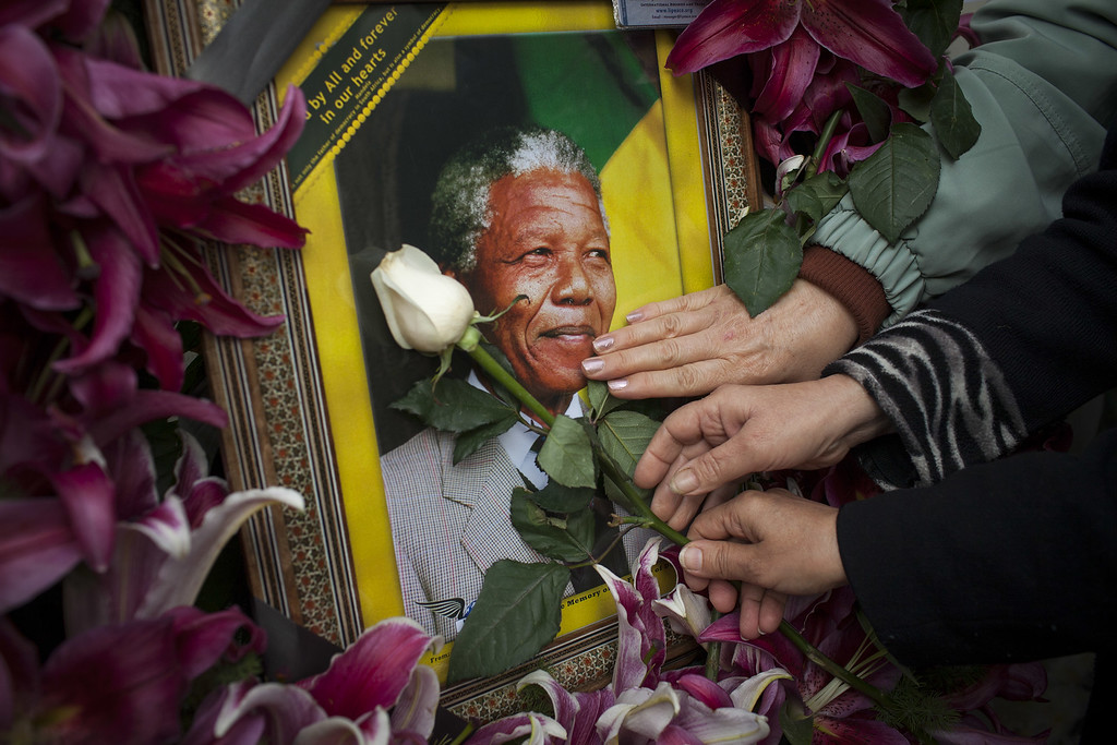 . Mourners gathered in front of the South African embassy to pay their respects to the memory of Nelson Mandela on December 7, 2013 in Tehran, Iran. Mandela, also known as Tata Madiba, passed away on the evening of December 5th at his home in Houghton at the age of 95. Mandela became South Africa\'s first black president after being jailed for decades for his activism against apartheid in a racially-divided South Africa. (Photo by Majid Saeedi/Getty Images)