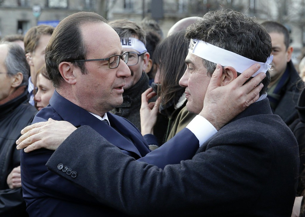 . TOPSHOTS French President Francois Hollande (L) comforts French columnist for Charlie Hebdo Dr Patrick Pelloux as they attend the solidarity march (Marche Republicaine) in the streets of Paris January 11, 2015. French citizens will be joined by dozens of foreign leaders, among them Arab and Muslim representatives, in a march on Sunday in an unprecedented tribute to this week\'s victims following the shootings by gunmen at the offices of the satirical weekly newspaper Charlie Hebdo, the killing of a police woman in Montrouge, and the hostage taking at a kosher supermarket at the Porte de Vincennes.     AFP PHOTO POOL PHILIPPE WOJAZERPHILIPPE WOJAZER/AFP/Getty Images