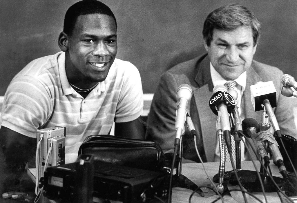 ". FILE - in this May 5, 1984 file photo, North Carolina guard Michael Jordan, left, and Tar Heels coach Dean Smith are shown at a news conference in Chapel Hill, N.C., where Jordan announced he would forfeit his final year of college eligibility to turn pro. Smith, the North Carolina basketball coaching great who won two national championships, died ""peacefully\"" at his home Saturday night, Feb. 7, 2015, the school said in a statement Sunday from Smith\'s family. He was 83. (AP Photo, File)"