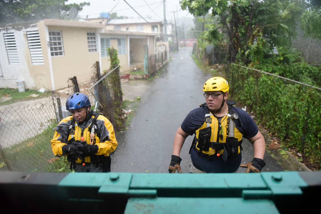 . Julio Feliciano (left, and Adrian Colon, right, both rescue staff members from the Municipal Emergency Management Agency toured the streets of the Matelnillo community searching for citizens in distress during the passage of Hurricane Irma through the northeastern part of the island in Fajardo, Puerto Rico, Wednesday, Sept. 6, 2017. The US territory was first to declare a state of emergency las Monday, as the National Hurricane Center forecast that the storm would strike the Island Wednesday. (AP Photo/Carlos Giusti)