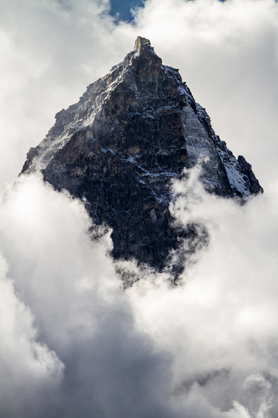 A solemn black Himalayan peak rises above swirling clouds below in Nepal