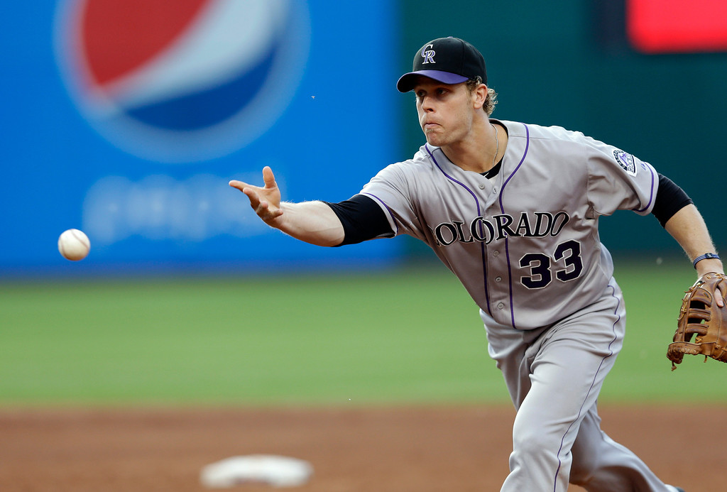 . Colorado Rockies first baseman Justin Morneau tosses to the pitcher covering first to get Cleveland Indians\' Jesus Aguilar on a grounder in the second inning of a baseball game Friday, May 30, 2014, in Cleveland. (AP Photo/Mark Duncan)
