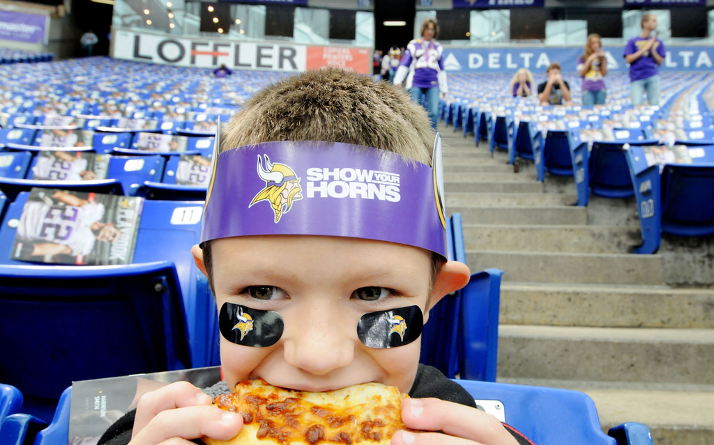 . Landon Styles, 8, of Harrisburg, S.D., chows down a pre-game slice as he watches the Vikings and Browns warm up before the game. The family made the four-hour drive from South Dakota to see a game in the Metrodome\'s final season. Sunday was Landon\'s first Vikings game. (Pioneer Press: Sherri LaRose-Chiglo)