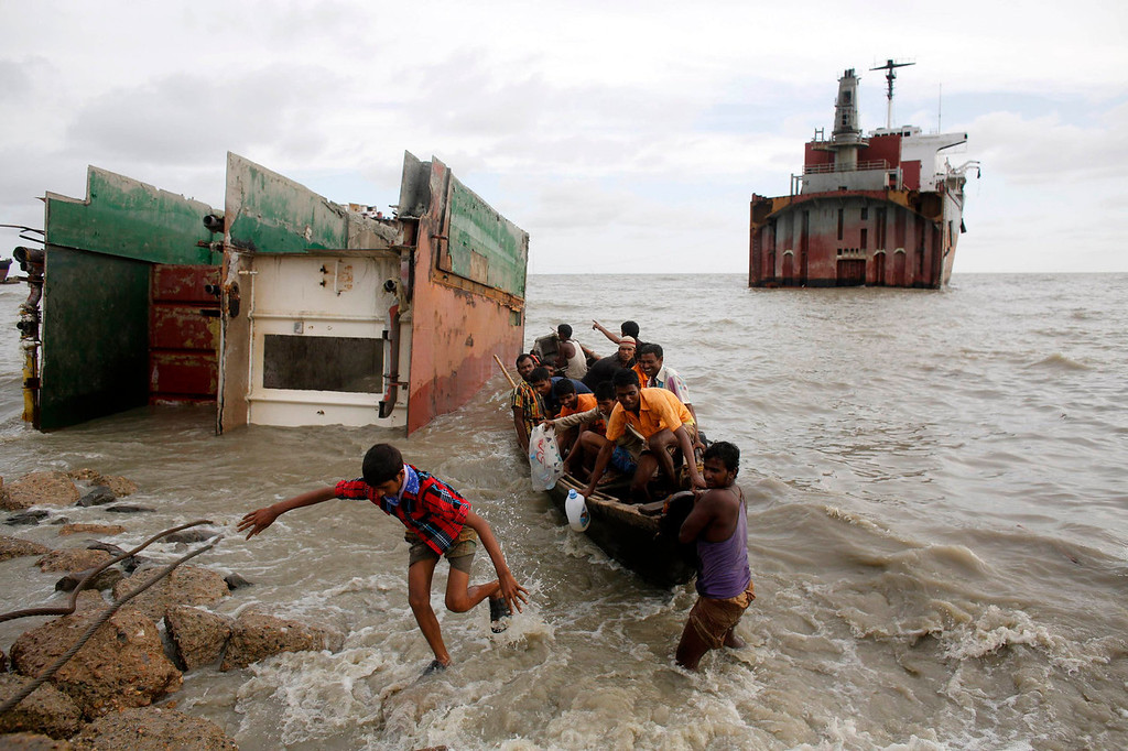. Workers disembark from a boat as they return from part of a wrecked ship after work at a ship-breaking yard in Chittagong, Bangladesh July 16, 2013. Bangladesh is dependent on ship-breaking for its domestic steel requirements. According to a report by the Bangladesh Institute of Labour Studies, around 30,000 workers are employed in the ship-breaking industry in Chittagong, a highly polluted coastal belt of around 20 km (12.4 miles), and environmental organizations have said that the number of accidents and casualties at the yard is believed to be the highest in the region. International attention has been focused on workers\' safety in Bangladesh since the disaster at Rana Plaza, a garment factory complex which collapsed in April, killing 1,132 workers.   REUTERS/Andrew Biraj