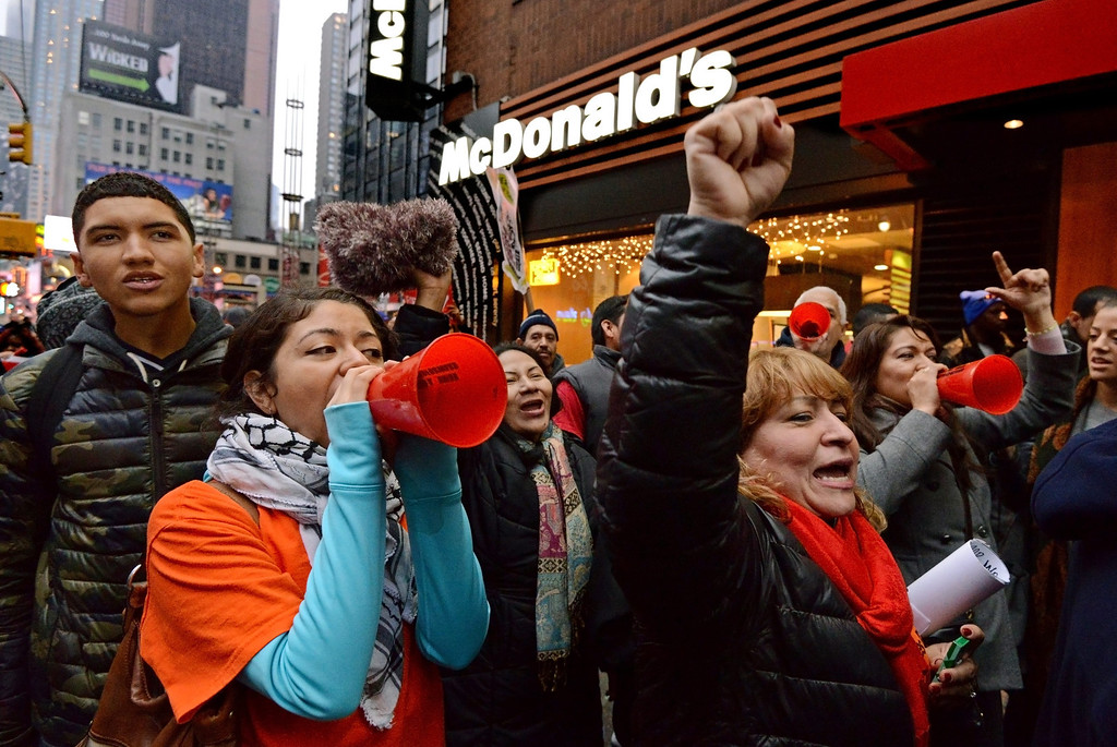 . Protesters shout slogans as workers and union members demonstrate calling for an increase in the minimum hourly wage to 15 US dollars and the right of workers to join unions, outside a McDonald\'s restaurant in New York, USA, 05 December 2013.  EPA/PETER FOLEY