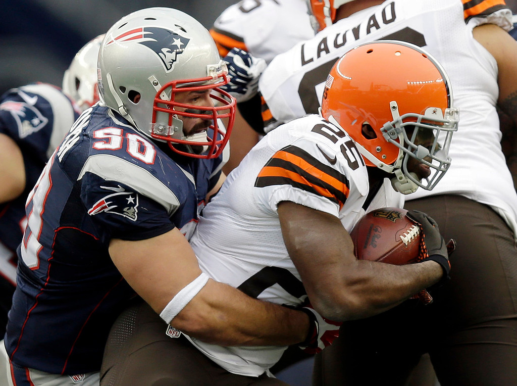 . New England Patriots defensive end Rob Ninkovich (50) tackles Cleveland Browns running back Chris Ogbonnaya (25) in the second quarter of an NFL football game on Sunday, Dec. 8, 2013, in Foxborough, Mass. (AP Photo/Steven Senne)