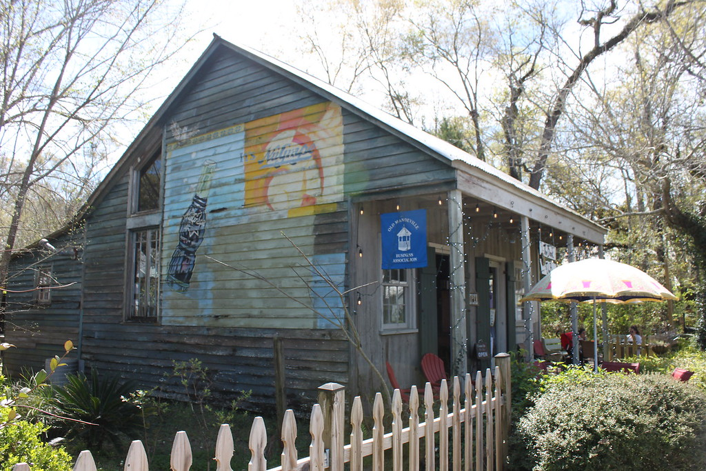 An old wooden cabin with faded painted advertisements on the side has been turned into a bookstore