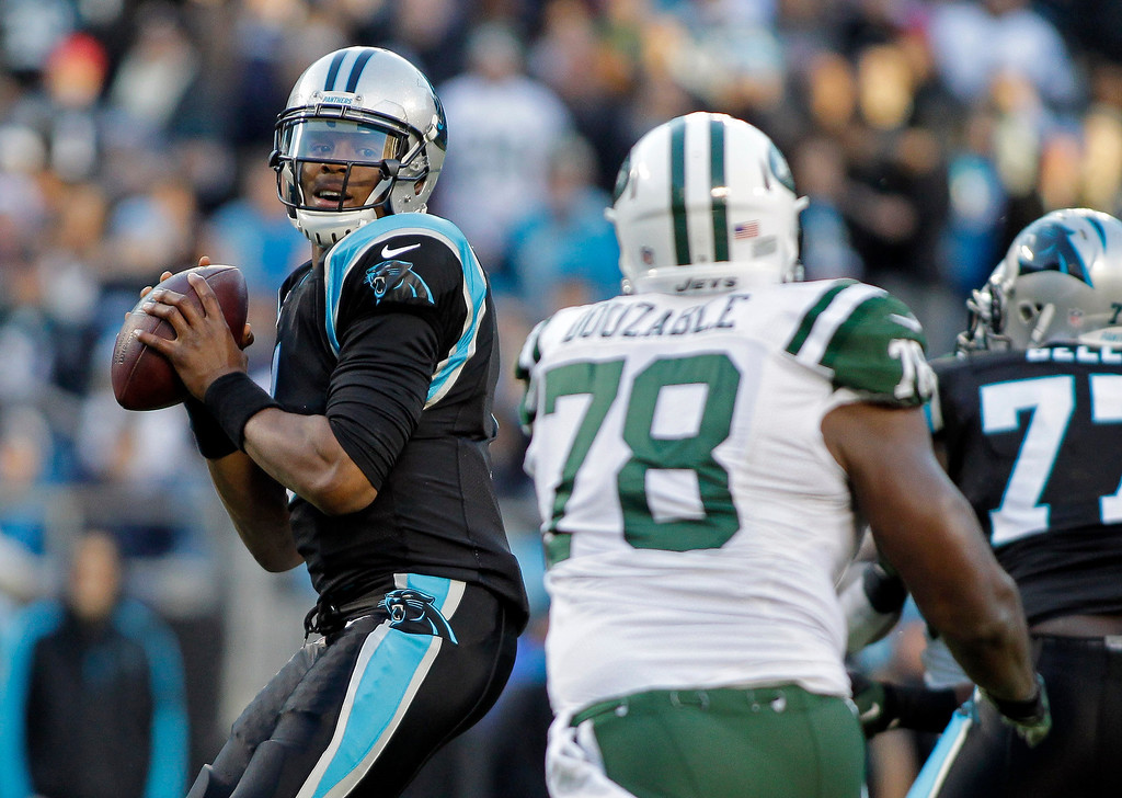 . Carolina Panthers quarterback Cam Newton, left, looks to pass under pressure from New York Jets\' Leger Douzable (78) during the first half of an NFL football game in Charlotte, N.C., Sunday, Dec. 15, 2013. (AP Photo/Bob Leverone)