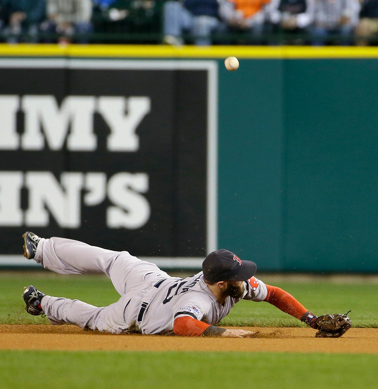 . Boston Red Sox second baseman Dustin Pedroia tries to field a ball hit by Detroit Tigers center fielder Austin Jackson in the fourth inning during Game 4 of the American League baseball championship series Wednesday, Oct. 16, 2013, in Detroit. (AP Photo/Matt Slocum)