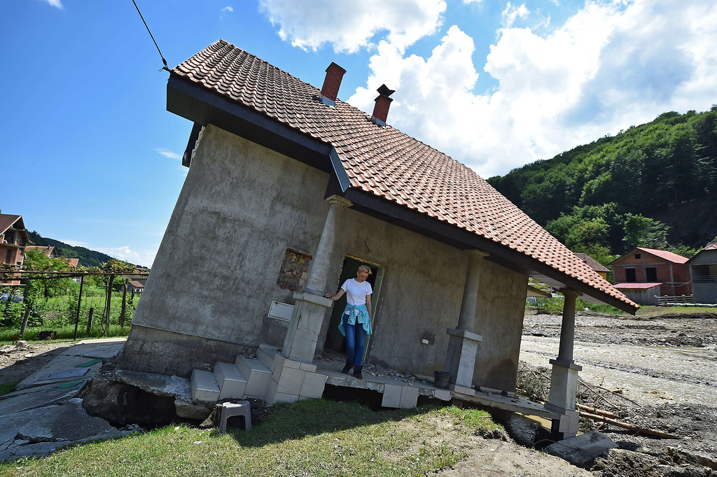 . Flood victim Pavlovic Oksana stands on the front porch of her house, damaged by flooding and landslide, in Krupanj, some 130 kilometers south west of Belgrade, on May 20, 2014, after the western Serbian town was hit with floods and landslides, cutting it off for four days. Serbia declared three days of national mourning on May 20 as the death toll from the worst flood to hit the Balkans in living memory rose and health officials warned of a possible epidemic.   AFP PHOTO / ANDREJ ISAKOVIC/AFP/Getty Images