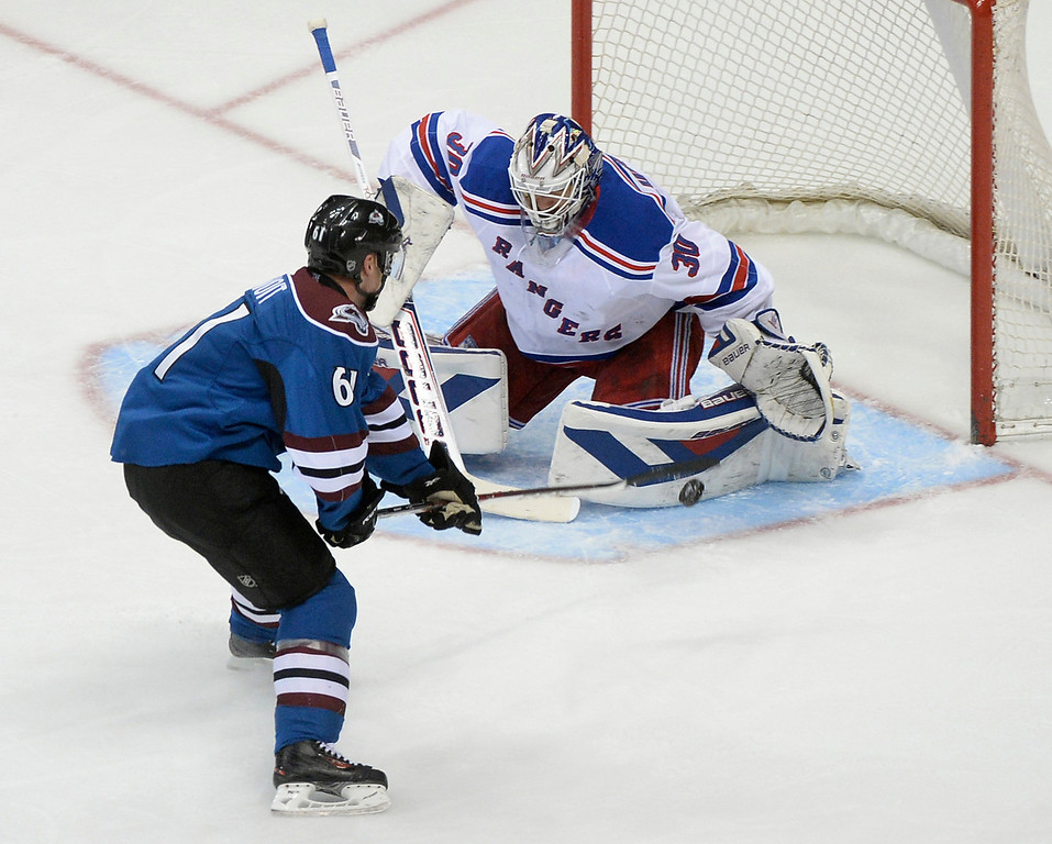 . Denver defenseman Andre Benoit (61) lifted a shot past New York goalie Henrik Lundqvist (30) in the second period. (Photo by Karl Gehring/The Denver Post)