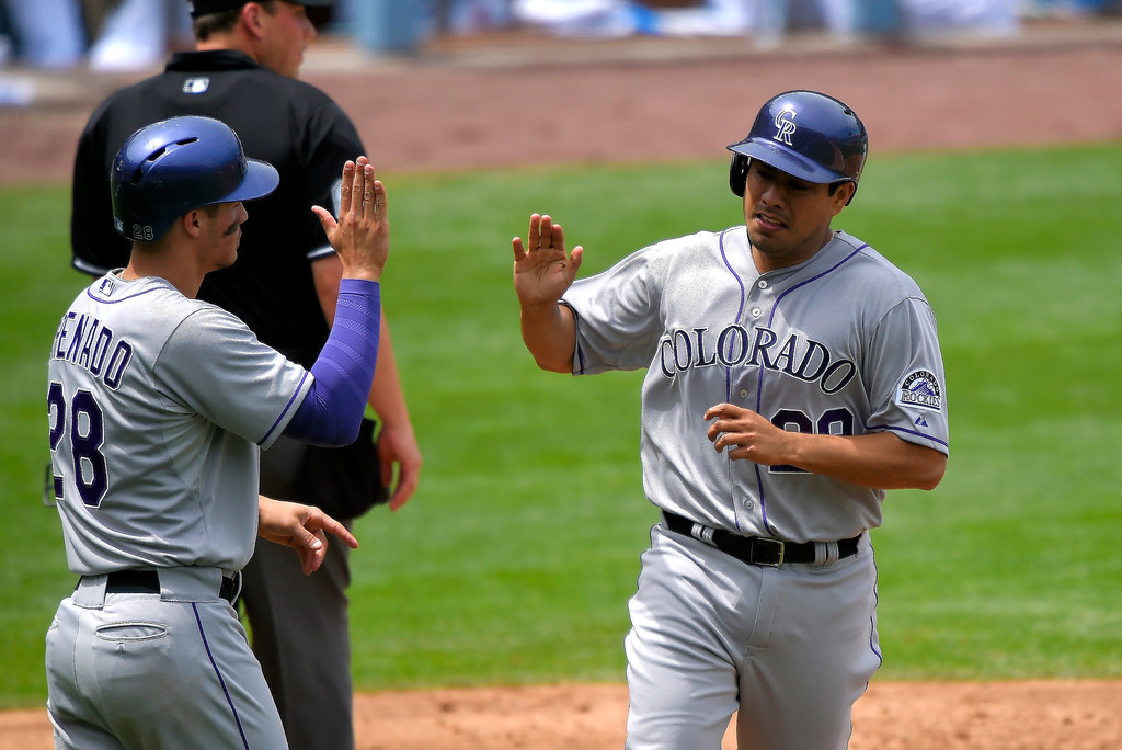 . Colorado Rockies\' Jorge De La Rosa, right, is congratulated by Nolan Arenado after they scored on a single by Brandon Barnes during the second inning of a baseball game against the Los Angeles Dodgers, Sunday, April 27, 2014, in Los Angeles. (AP Photo/Mark J. Terrill)