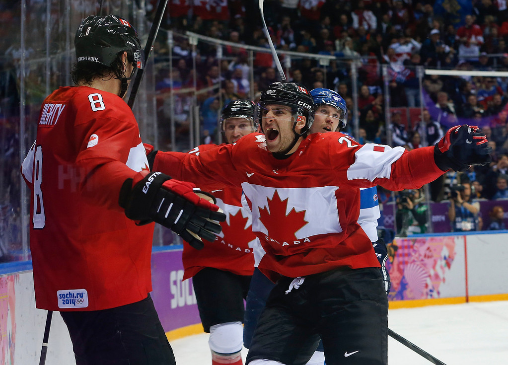 . Canada forward John Tavares, right, and forward Jeff Carter, second from left, celebrate with defenseman Drew Doughty (8) after Doughty scored a sudden death overtime goal against Finland during a men\'s ice hockey game at the 2014 Winter Olympics, Sunday, Feb. 16, 2014, in Sochi, Russia. Canada won 2-1. (AP Photo/Mark Humphrey)