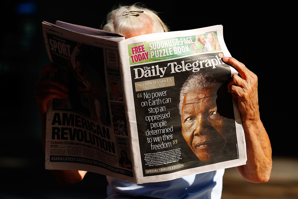 . A woman reads an Australian newspaper  reporting on the death of former South African President Nelson Mandela on December 7, 2013 in Sydney, Australia. Mandela was a leader that helped conquer apartheid in racially divided South Africa after being jailed for his activism for decades. He was South Africa\'s first black president. He died yesterday at the age of 95.  (Photo by Brendon Thorne/Getty Images)