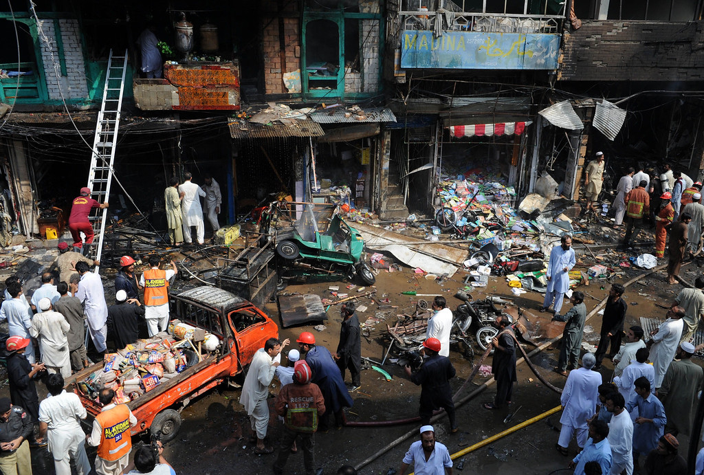 . Pakistani security officials and volunteers gather at the site of a bomb explosion in the busy Kissa Khwani market in Peshawar on September 29, 2013.   AFP PHOTO / A.  MAJEED/AFP/Getty Images